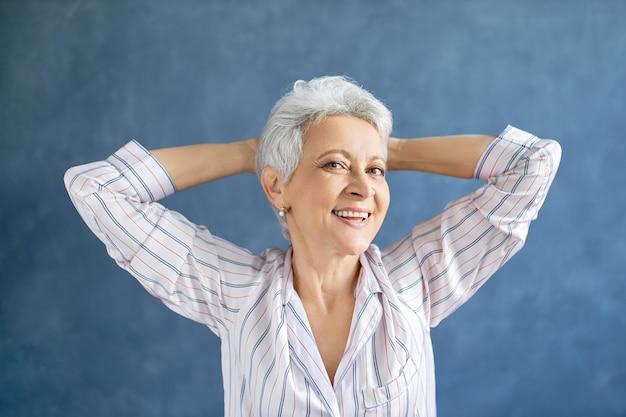 Retrato de hermosa mujer de mediana edad en elegante pijama de rayas estirando el cuerpo después de despertar temprano en la mañana