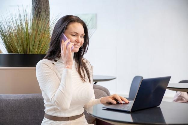 Retrato de hermosa mujer de mediana edad sonriendo y hablando por teléfono en la computadora portátil en la oficina