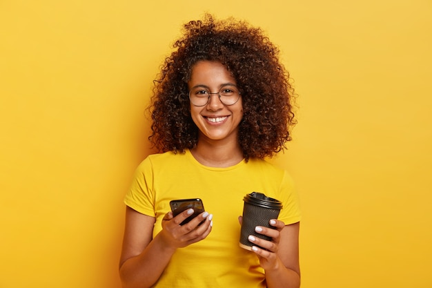 Retrato de hermosa mujer milenaria sostiene un teléfono inteligente y bebe café para llevar, sonríe agradablemente, usa una camiseta amarilla, pregunta el número para reunirse más tarde