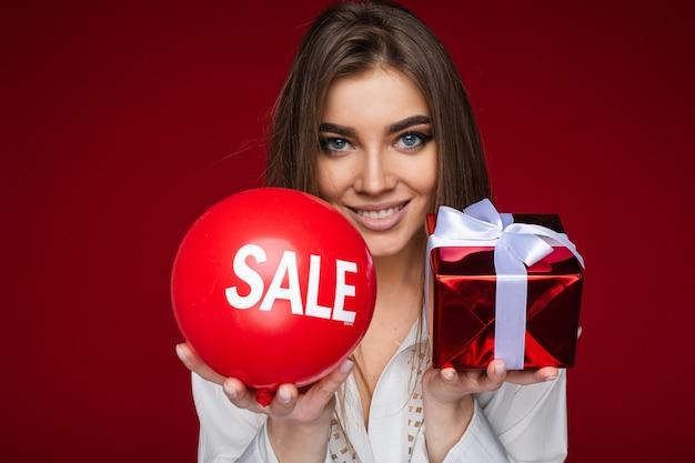 Retrato de hermosa mujer morena con camisa blanca que ofrece globo rojo con etiqueta de venta y regalo rojo envuelto con blanco para inclinarse ante la cámara.
