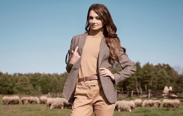 Retrato de una hermosa mujer morena en una elegante chaqueta marrón a cuadros posando en el paisaje campestre Foto Premium