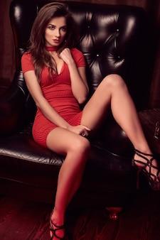 Retrato de hermosa mujer morena joven en vestido rojo sentado en una silla de cuero