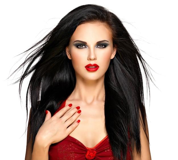 Retrato de una hermosa mujer morena con uñas y labios rojos, aislado sobre fondo blanco.