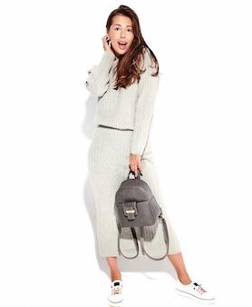 Retrato de hermosa mujer morena linda modelo en ropa casual suéter gris otoño sin maquillaje aislado en blanco con bolso
