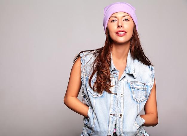 Retrato de hermosa mujer morena linda modelo en ropa casual de verano jeans sin maquillaje en gorro púrpura aislado en gris
