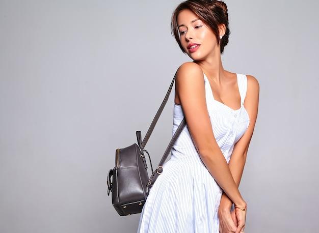 Retrato de hermosa mujer morena linda modelo en vestido casual de verano sin maquillaje aislado en gris con bolso
