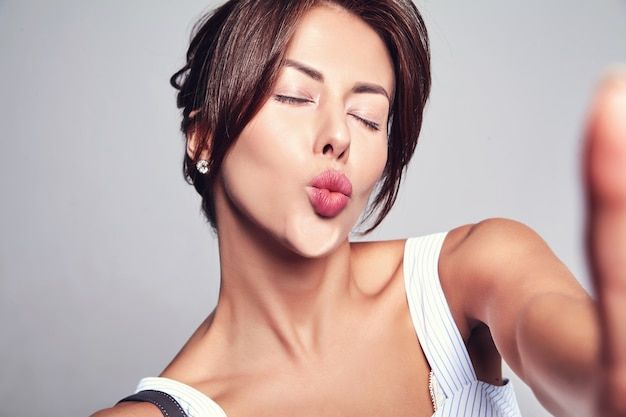 Retrato de hermosa mujer morena linda modelo en vestido casual de verano sin maquillaje haciendo foto selfie en teléfono aislado en gris con bolso. dando beso de aire