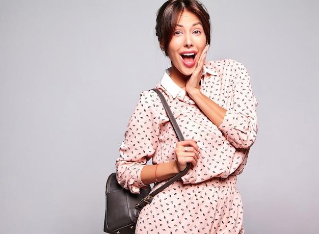Retrato de hermosa mujer morena linda sorprendida modelo en ropa casual de verano sin maquillaje aislado en la pared gris con bolso