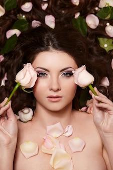 Retrato de hermosa mujer morena con pelo largo y rizado y flores