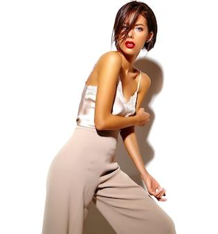 Retrato de hermosa mujer morena sensual chica en elegante ropa clásica blanca y pantalones anchos sobre fondo blanco.