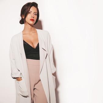 Retrato de hermosa mujer morena sensual. chica en ropa clásica beige elegante y pantalones anchos. modelo aislado en blanco