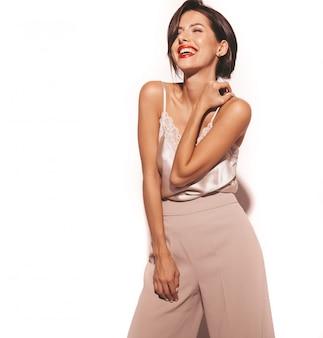 Retrato de hermosa mujer morena sensual sonriente. chica en ropa clásica beige elegante y pantalones anchos. modelo aislado en blanco