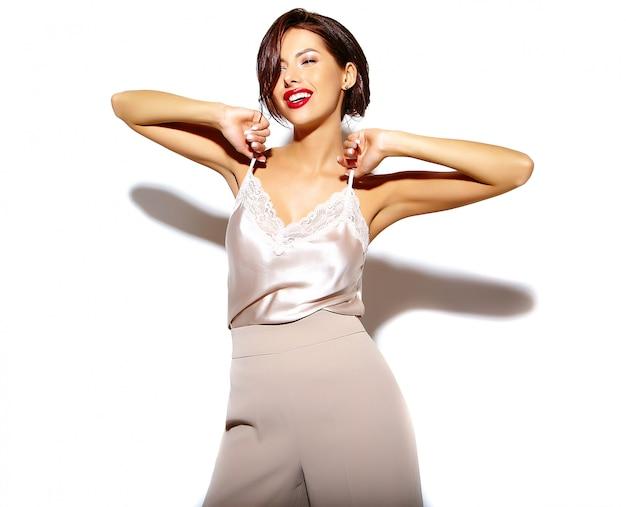 Retrato de hermosa mujer morena sexy linda feliz con labios rojos en amplios pantalones clásicos sobre fondo blanco.