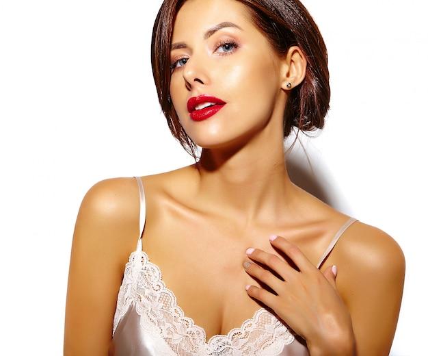 Retrato de hermosa mujer morena sexy linda feliz con labios rojos en pijama lencería sobre fondo blanco.