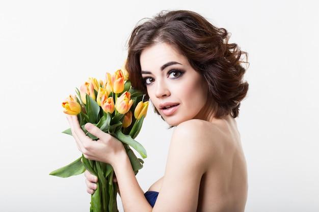 Retrato de hermosa mujer morena con tulipanes flores.