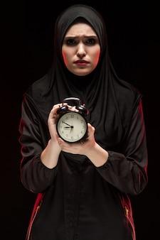 Retrato de hermosa mujer musulmana joven asustada grave asustada vistiendo hijab negro con reloj despertador sobre fondo negro