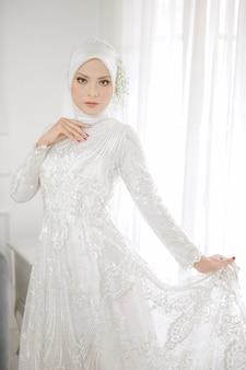 Retrato de hermosa mujer musulmana con vestido de novia blanco