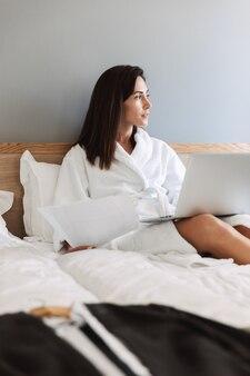 Retrato de hermosa mujer de negocios adulta en bata de baño blanca trabajando con documentos en papel y portátil mientras está acostado en la cama en el apartamento