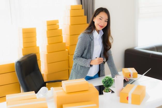 Retrato hermosa mujer de negocios asiática joven trabajar desde casa con teléfono móvil portátil con caja de cartón lista para enviar