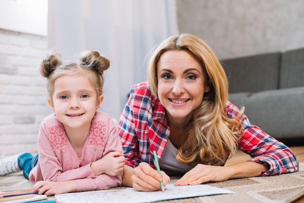 Retrato de hermosa mujer con niña dibujando en casa