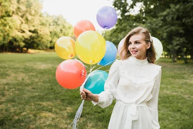 Retrato hermosa mujer oudoors con globos