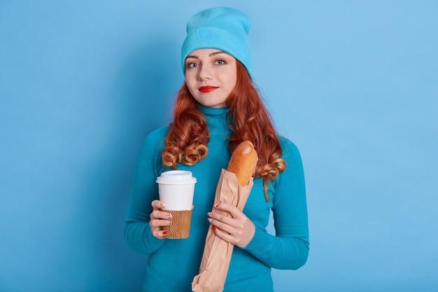 Retrato de hermosa mujer pelirroja europea con gorra y suéter casual