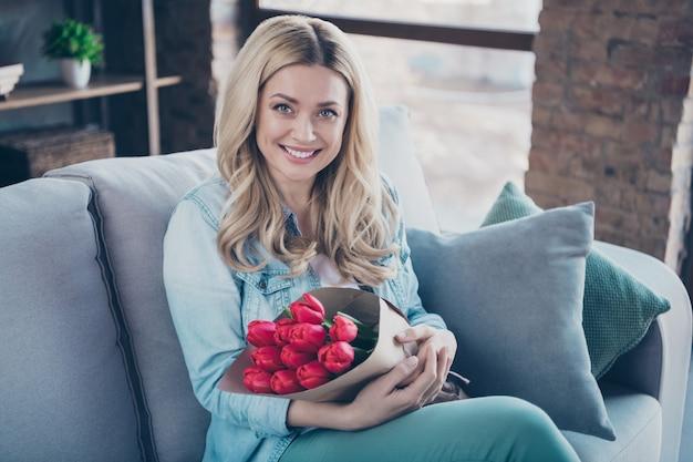 Retrato de hermosa mujer de pelo ondulado sentado diván sosteniendo en las manos flores rojas