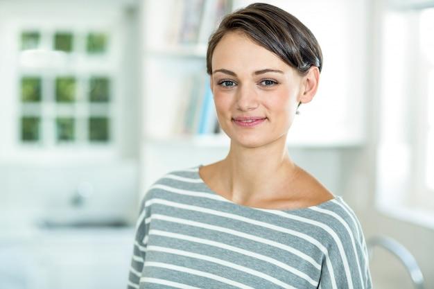 Retrato de hermosa mujer de pie en la cocina
