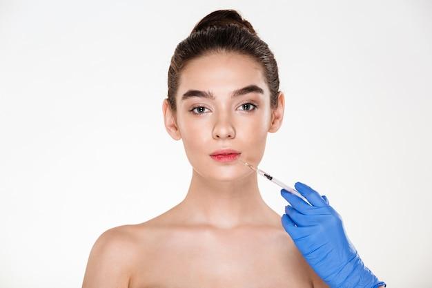 Retrato de hermosa mujer recibiendo inyección en sus labios con botox teniendo cirugía plástica en clínica