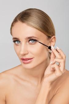 Retrato de hermosa mujer rubia aplicando delineador líquido con pincel. maquillaje natural.
