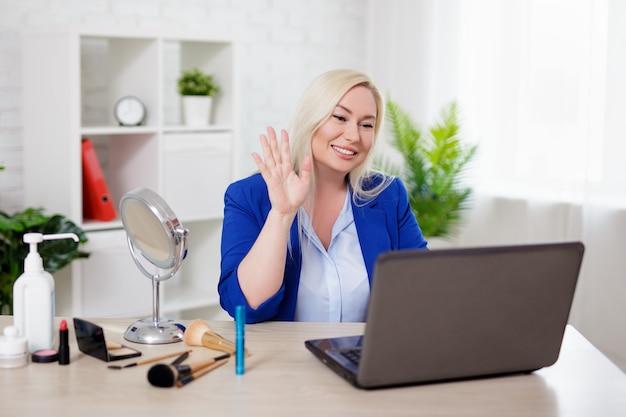 Retrato de hermosa mujer rubia blogger de belleza usando laptop y hablando con sus suscriptores sobre maquillaje