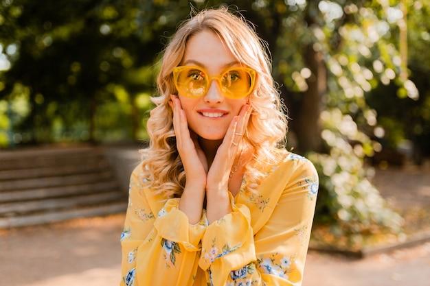 Retrato de hermosa mujer rubia con estilo emocional en blusa amarilla con gafas de sol, expresión divertida cara loca