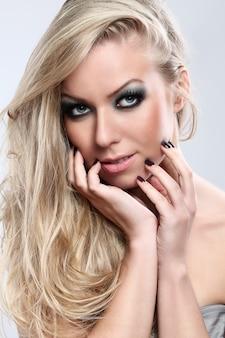 Retrato de hermosa mujer rubia con maquillaje oscuro
