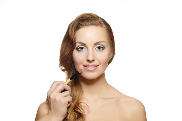 Retrato de hermosa mujer rubia con pelo largo y pincel de maquillaje cerca de cara atractiva