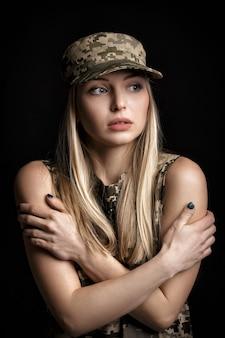 Retrato de una hermosa mujer rubia soldados en traje militar sobre fondo negro. frío y desesperación