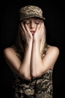 Retrato de una hermosa mujer rubia soldados en traje militar sobre fondo negro. tristeza y desesperación