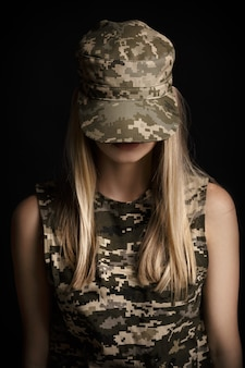 Retrato de una hermosa mujer rubia soldados en traje militar sobre fondo negro