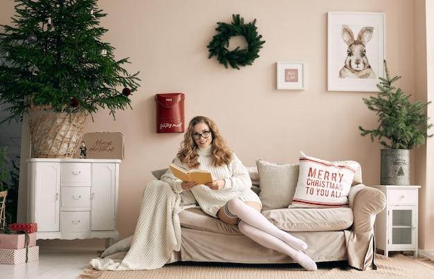 Retrato de hermosa mujer rubia en suéter de lana blanco y gafas leyendo un libro en un acogedor interior decorado con luz