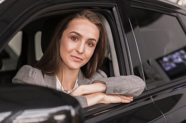 Retrato de hermosa mujer sentada en un auto