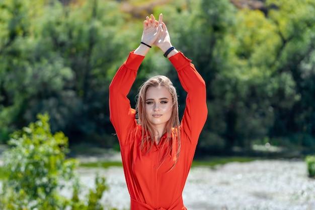 Retrato de la hermosa mujer sexy con cabello largo y rubio. chica joven de moda en vestido rojo posando en la naturaleza sobre un fondo de río con pelo volador. dos manos arriba.