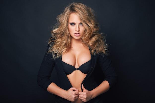 Retrato de hermosa mujer sexy rubia en negro