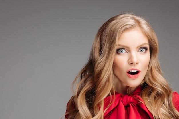 Retrato de hermosa mujer sorprendida en blusa roja con gran lazo.