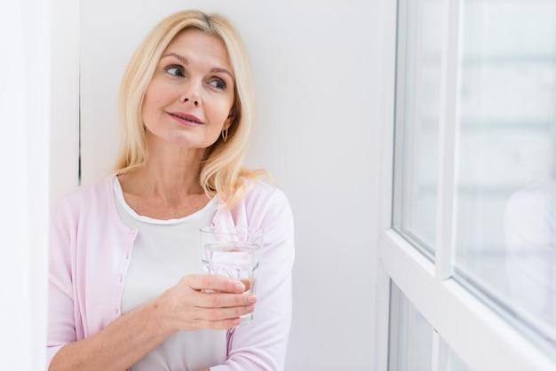 Retrato de hermosa mujer sosteniendo un vaso de agua