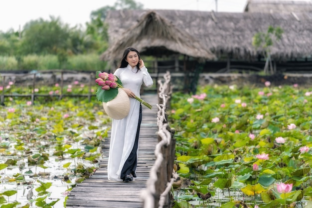 Retrato de hermosa mujer vietnamita con sombrero tradicional de vietnam sosteniendo el loto rosa
