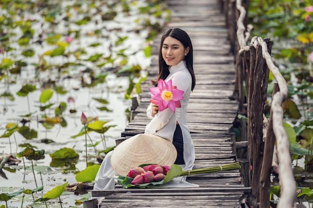 Retrato de hermosa mujer vietnamita con sombrero tradicional de vietnam