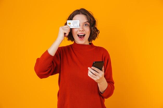 Retrato de hermosa mujer vistiendo suéter con teléfono celular y tarjeta de crédito mientras está de pie aislado en amarillo
