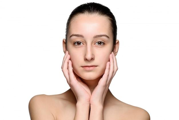 Retrato de hermosa niña acariciando su rostro con una piel sana
