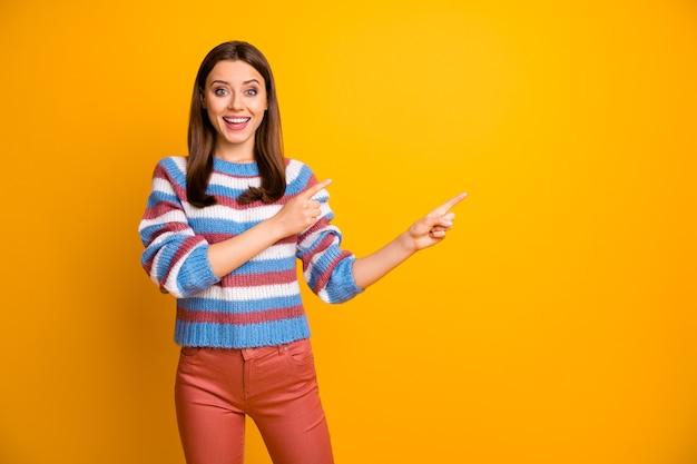 Retrato de hermosa niña alegre mostrando anuncio de espacio de copia