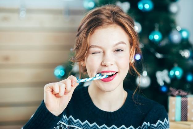 Retrato de hermosa niña con bastón de caramelo cerca de la cara sobre fondo de árbol de navidad