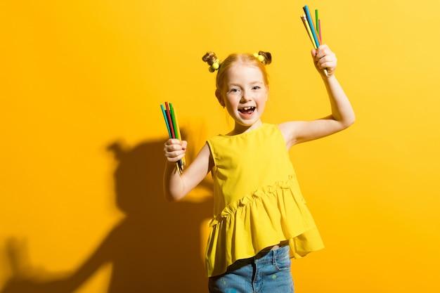 Retrato de una hermosa niña en una blusa amarilla y pantalones de mezclilla.